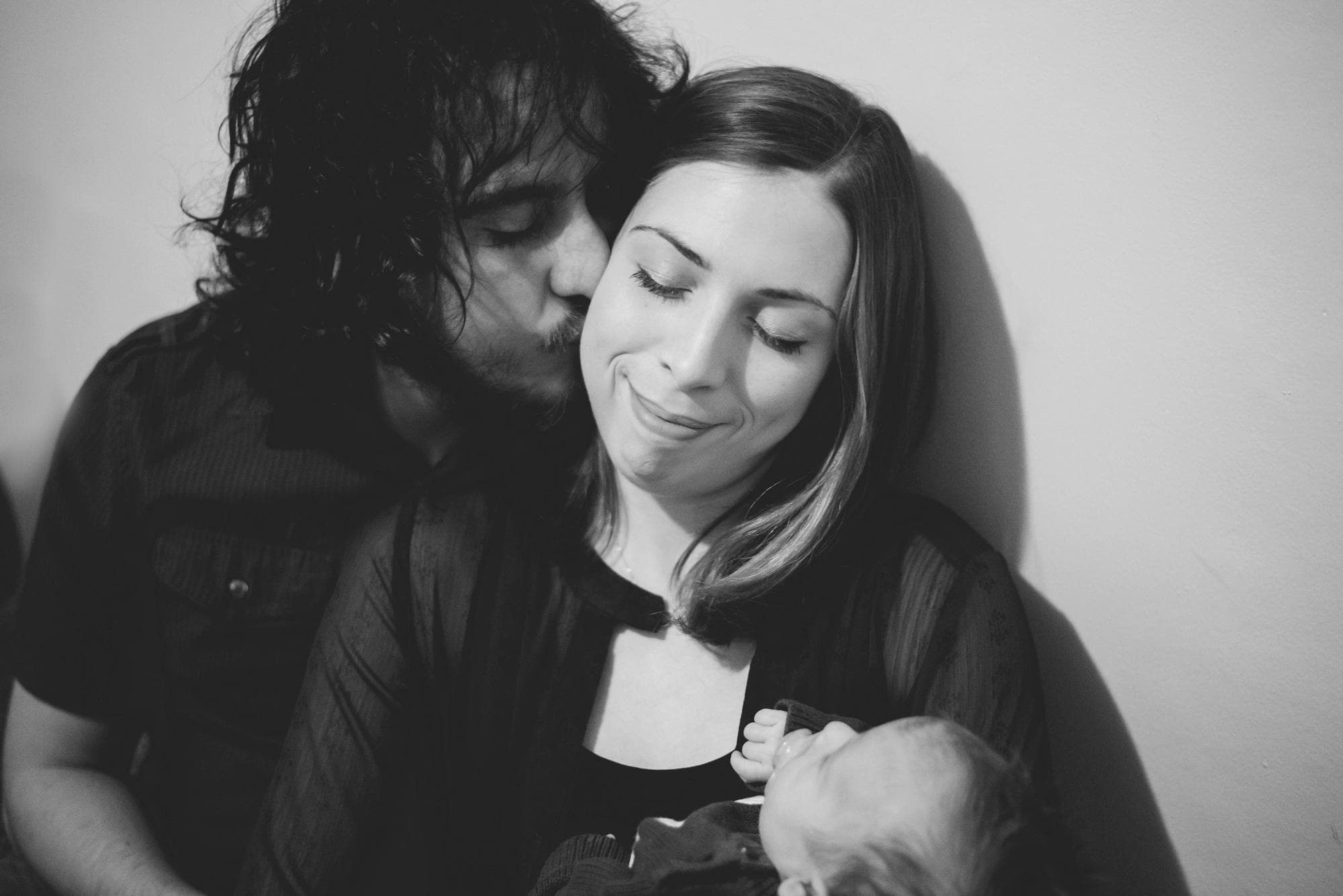 Newborn lifestyle session dad kissing mom