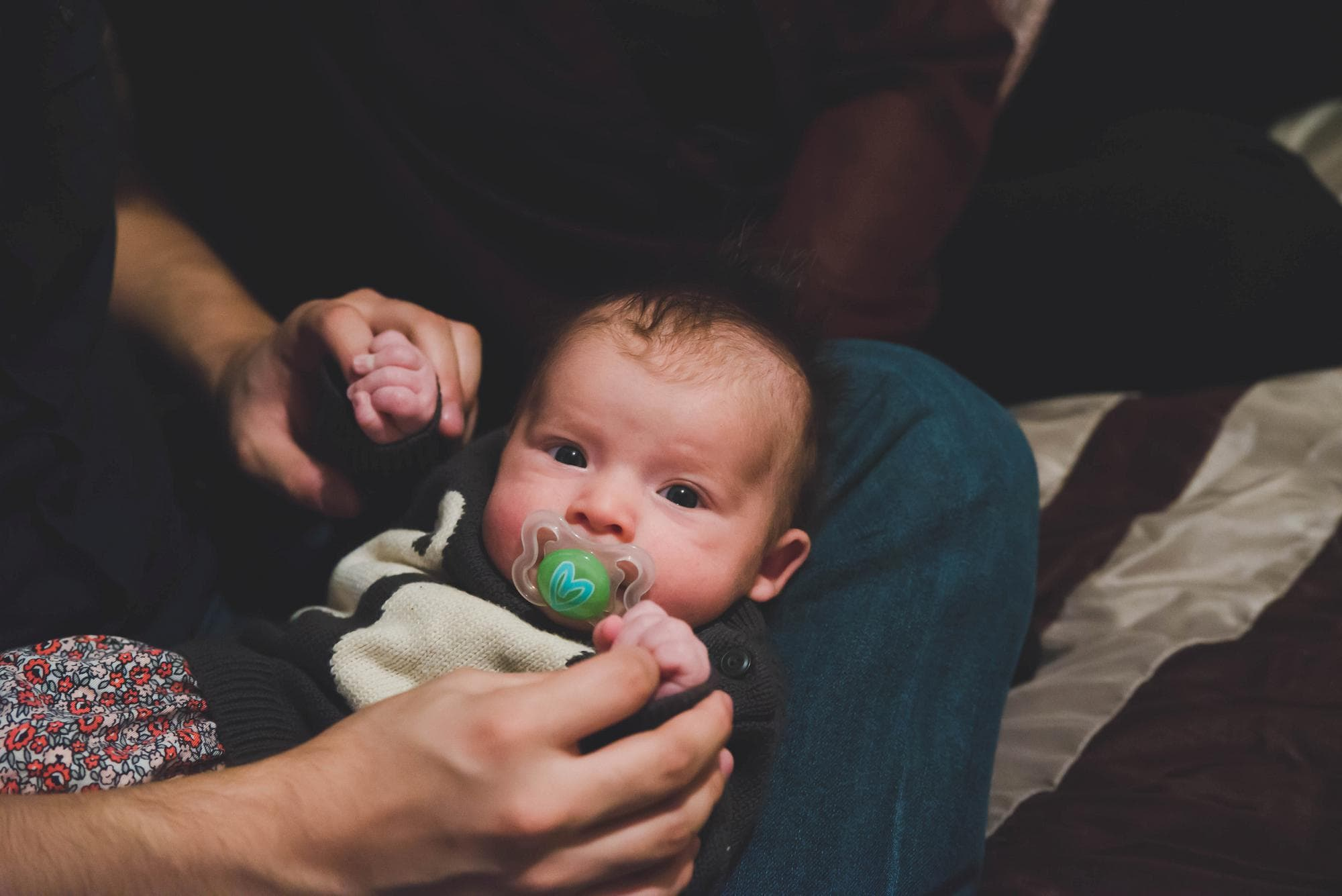 Newborn girl looking at the camera holding dad's hands lifestyle session