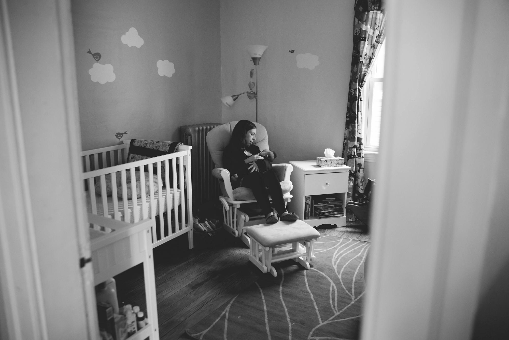 Mom with newborn in glider in nursery lifestyle session