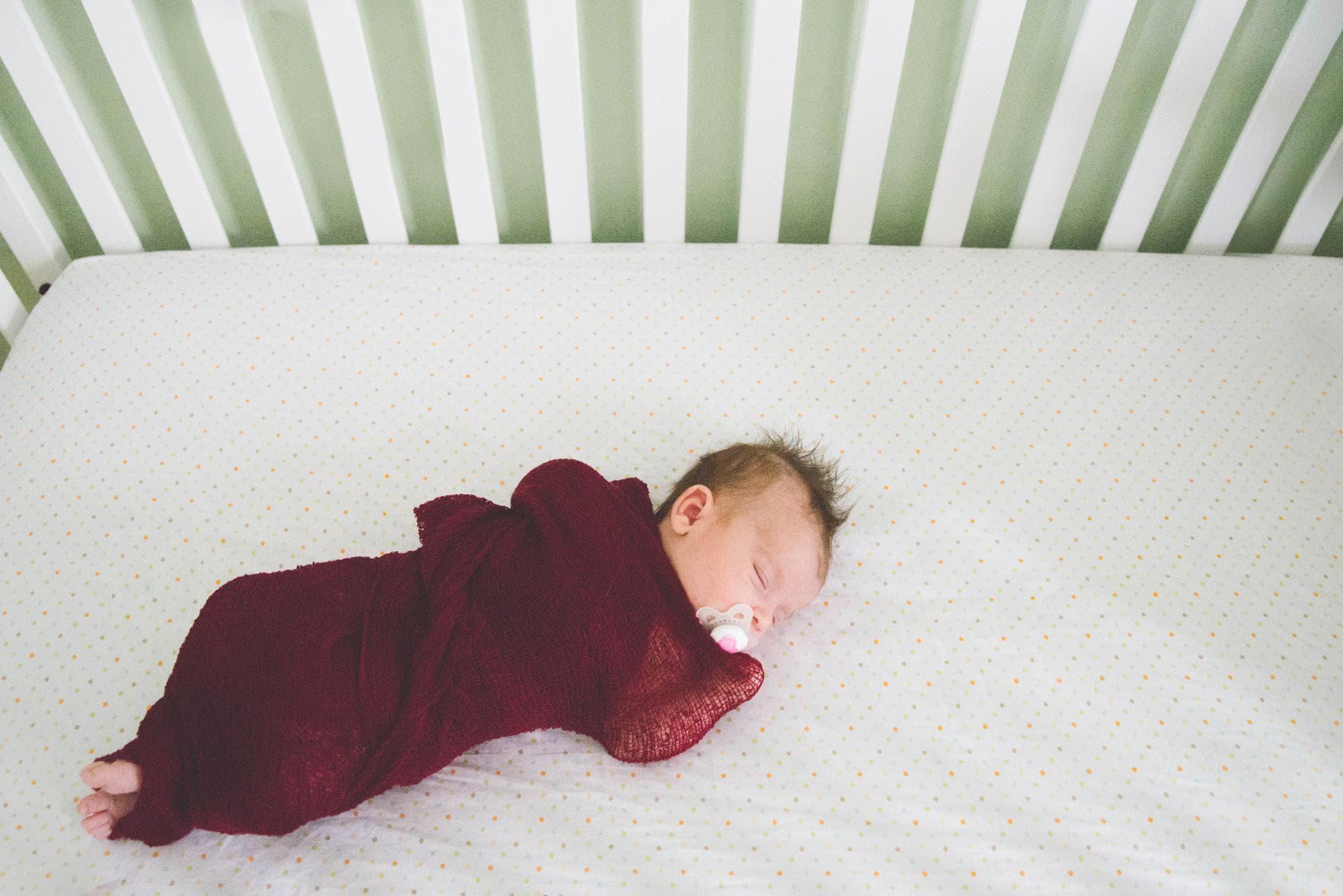 newborn girl lying in crib lifestyle session
