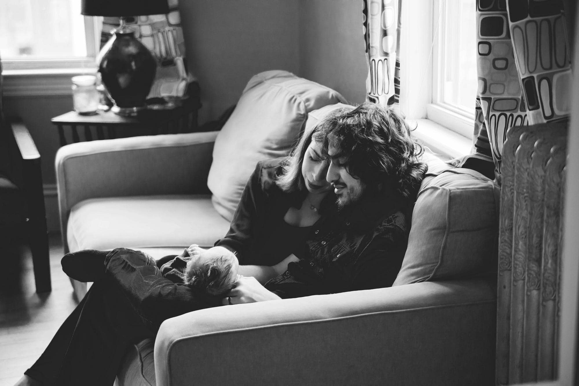 mom and dad cuddling newborn on couch lifestyle session