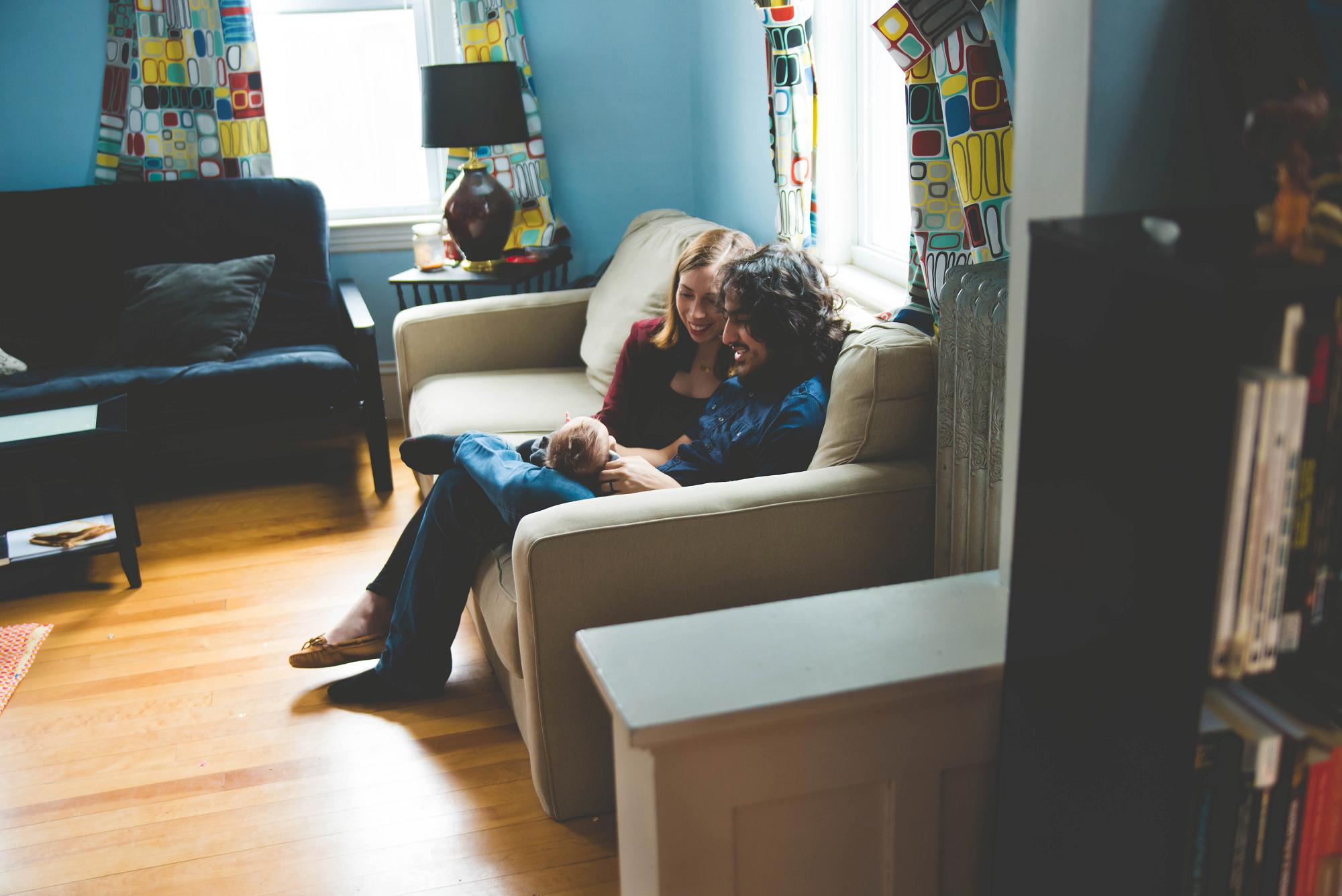 Parents with newborn on he couch in living room lifestyle session