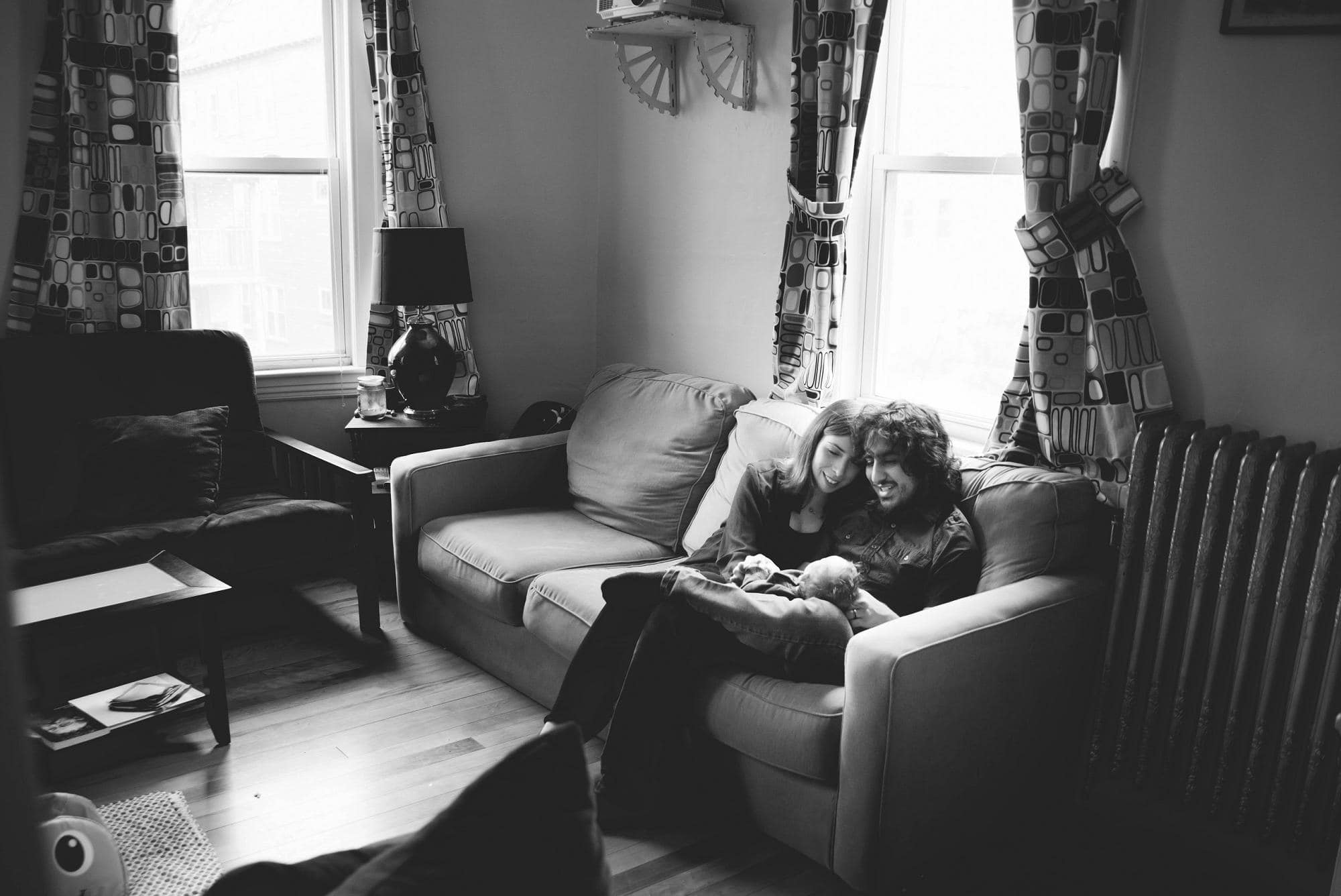 Wide view of parents on couch with newborn baby lifestyle session