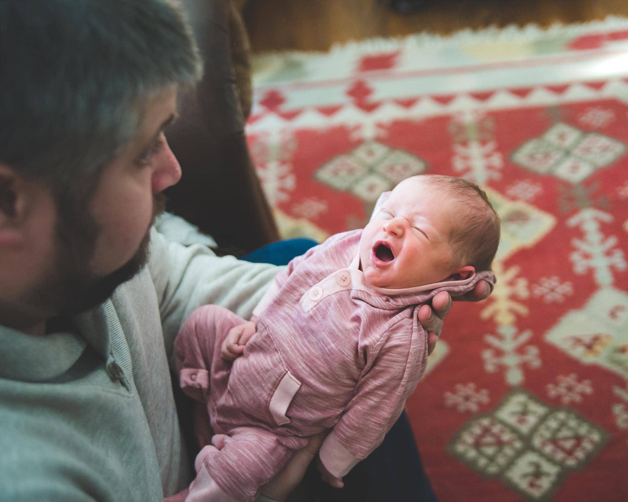 dad-holding-yawning-newborn