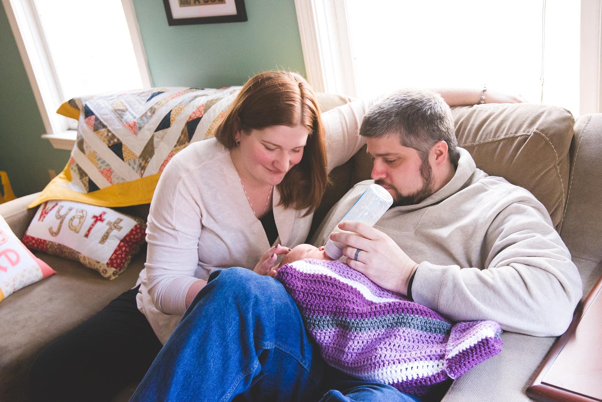 mom-dad-feeding-newborn-couch-lifestyle