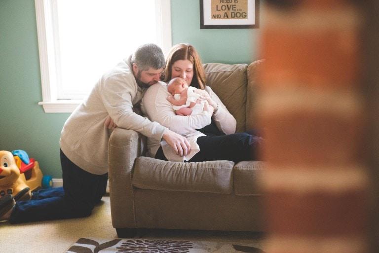 mom-dad-newborn-hug-couch-peek-lifestyle