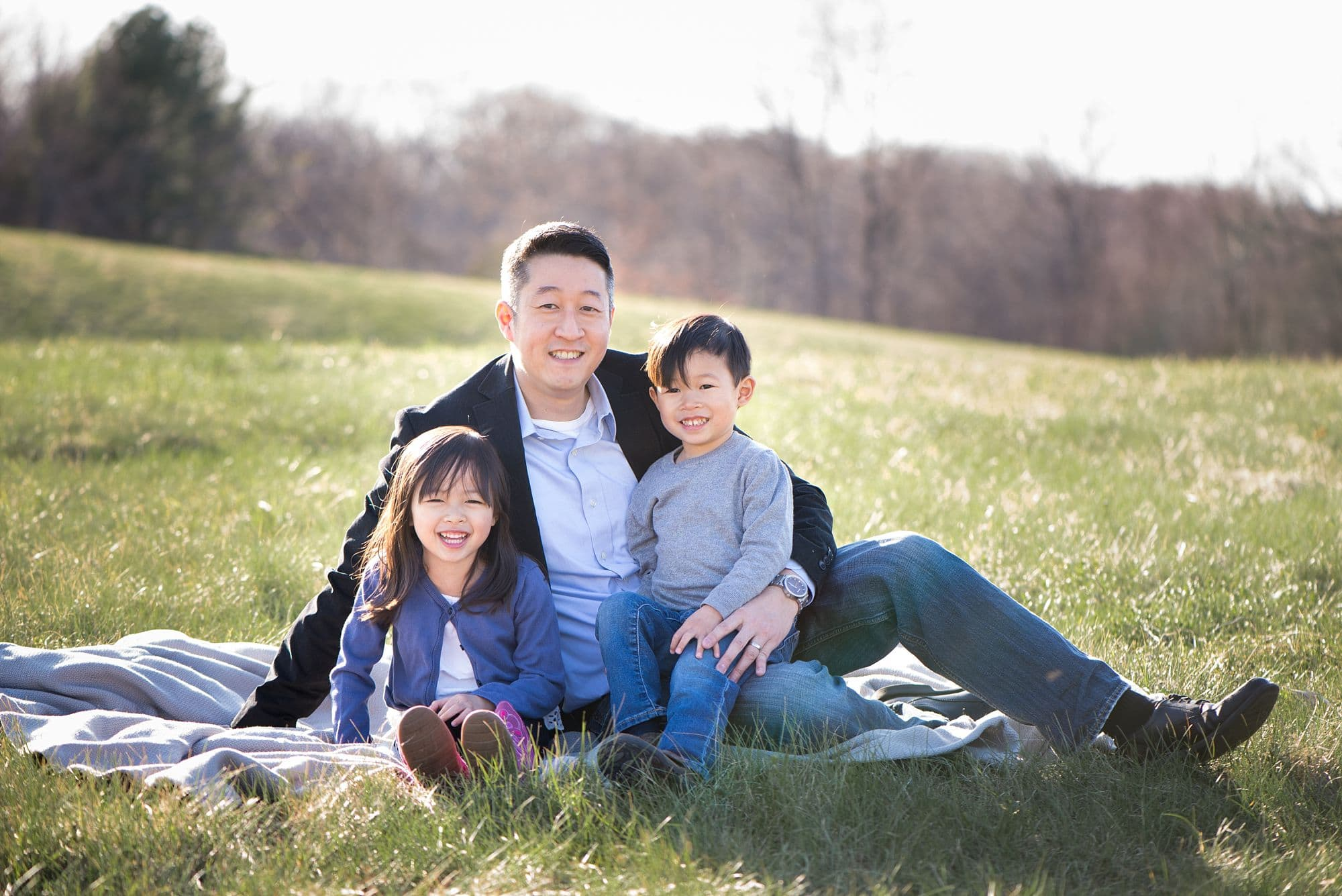 Outdoor photo of dad sitting with 2 young kids in his lap