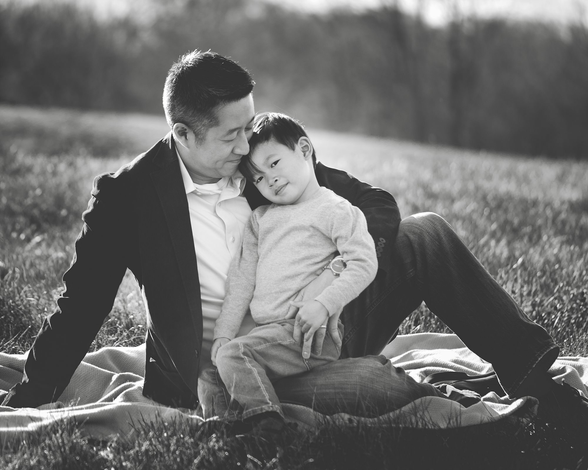 Dad holding toddler son on his lap and looking down at him