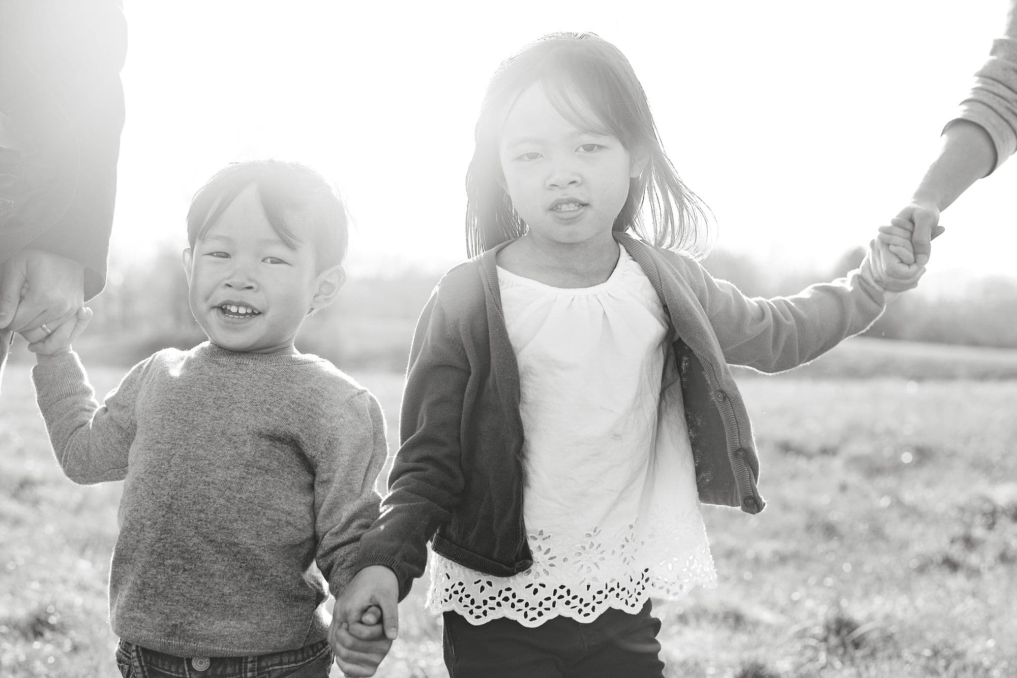 Boy and girl siblings holding hands in black and white
