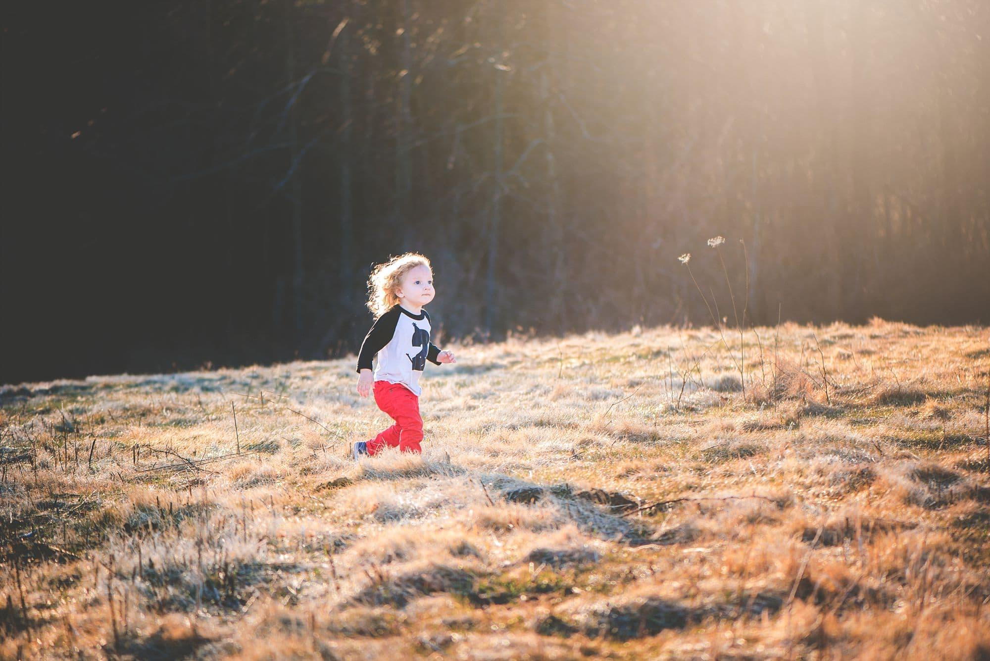 Child running through a sunlight field during golden hour
