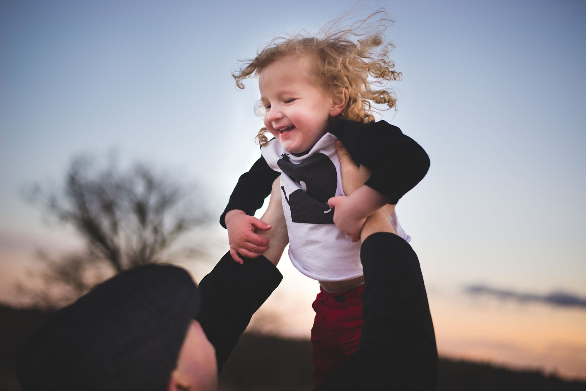 Toddler with long curly hair laughs as he is tossed into the air at twilight