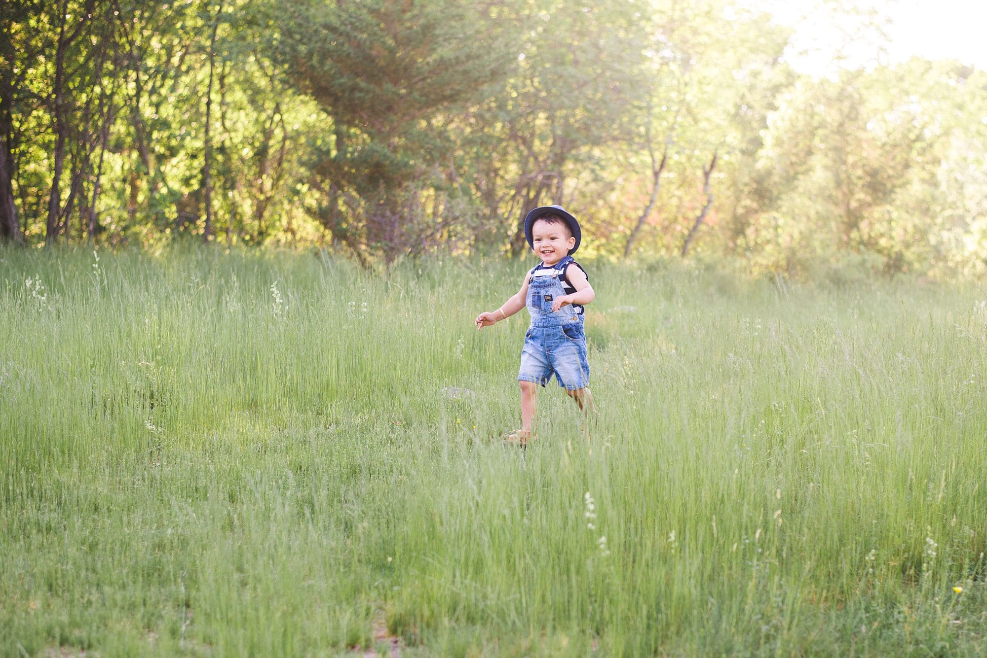 Little boy toddler running through a grassy field in his blue overalls and fedora during golden hour