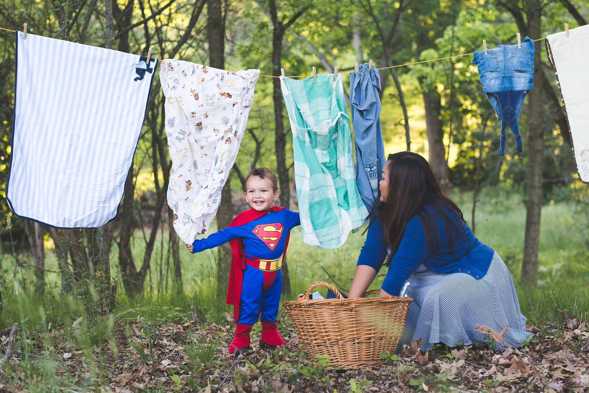 Mommy hanging up the wash on a laundry line with the help of superman toddler in costume