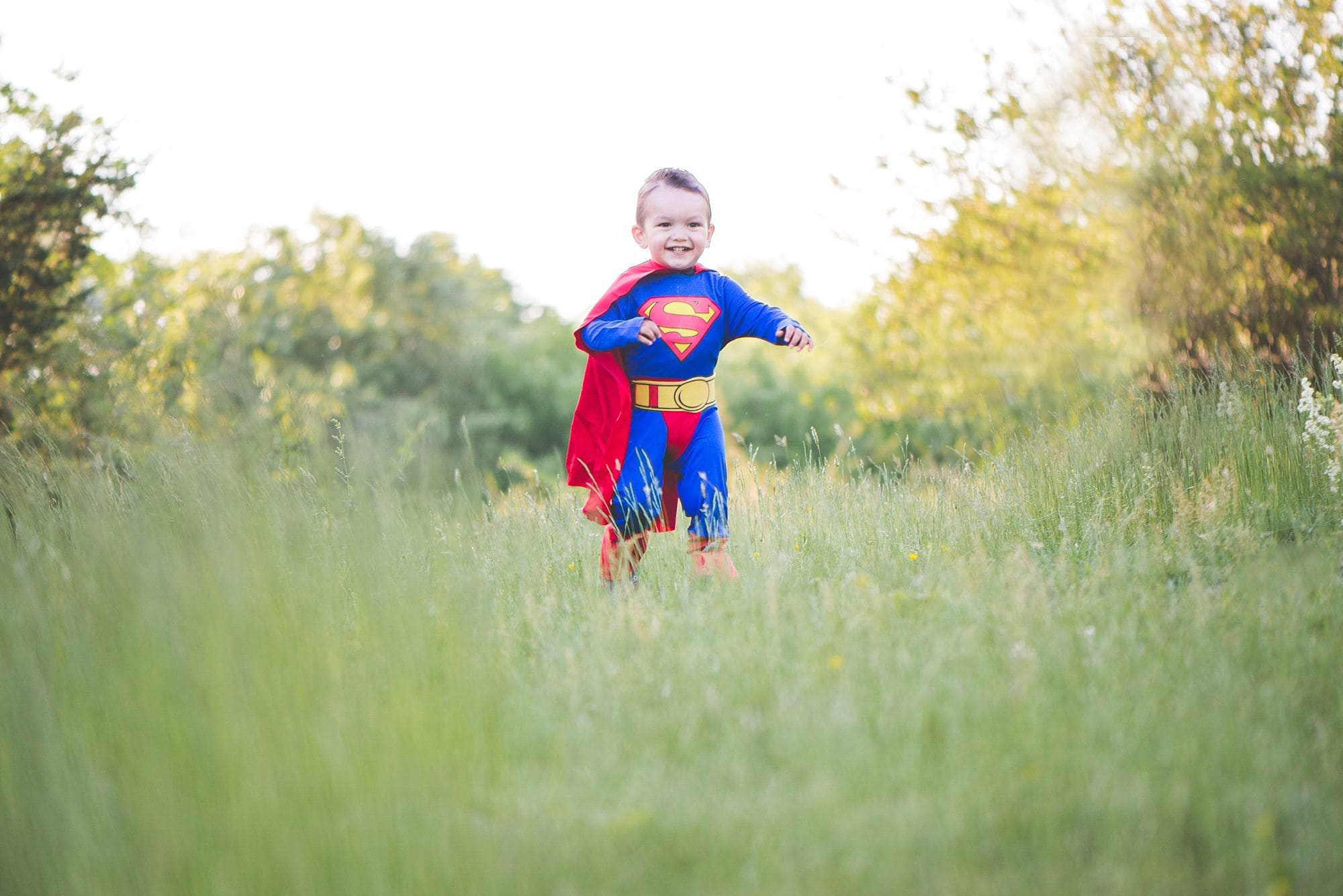 Little boy in superman costume playing n grassy field during golden hour