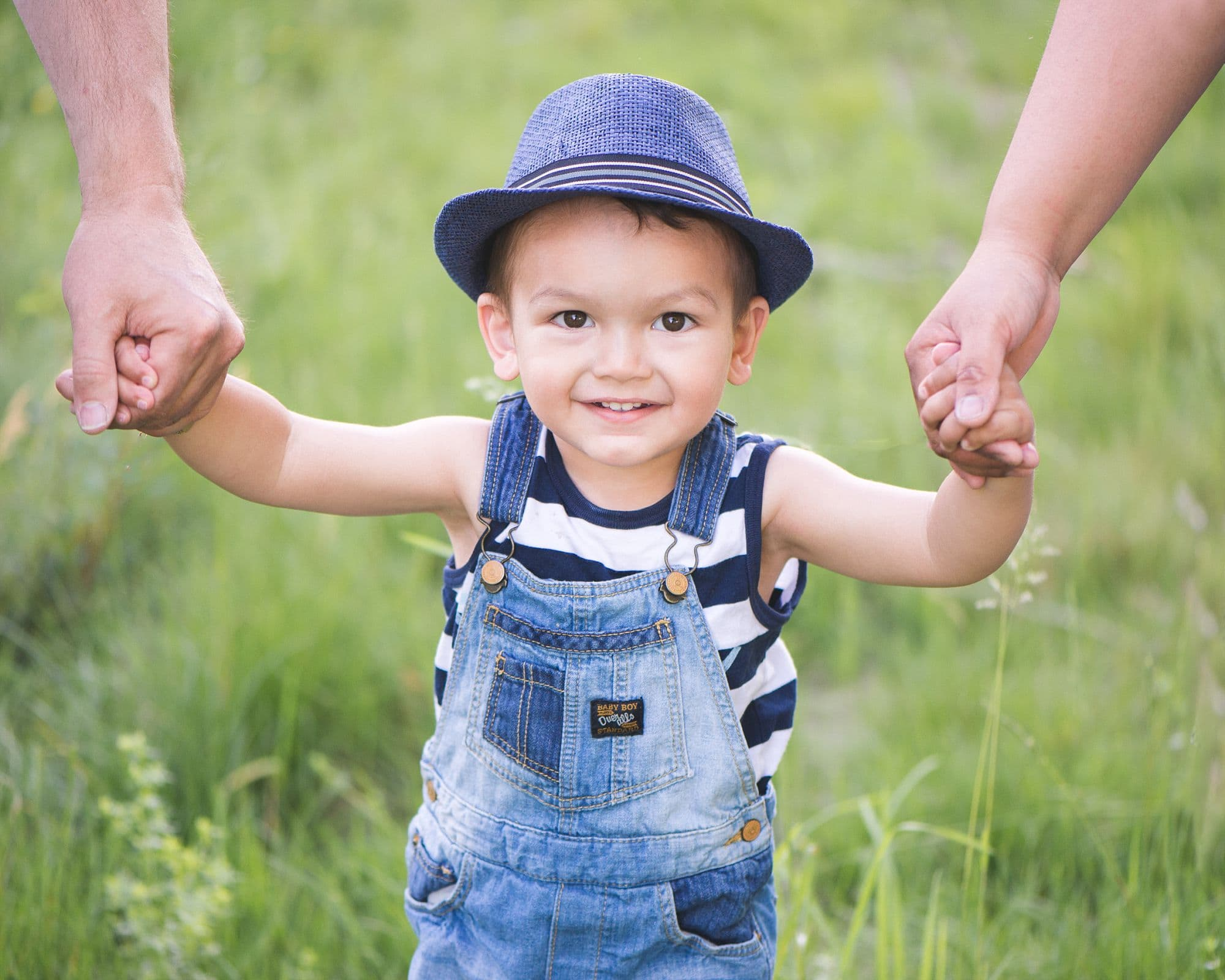 Adorable little boy in fedora and overalls holds mom and dad's hands on each side as he grins at the camera