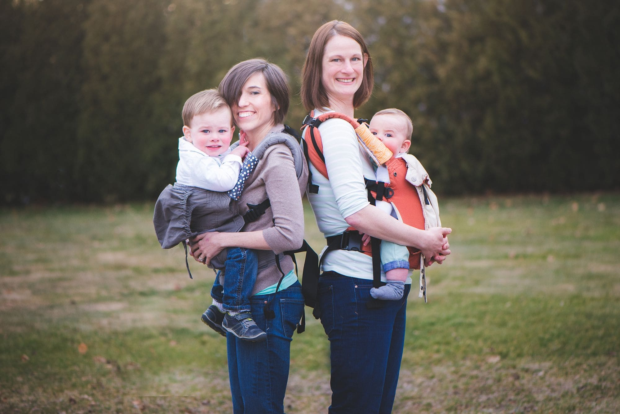 Two moms babywearing their toddler and baby in soft structured carriers