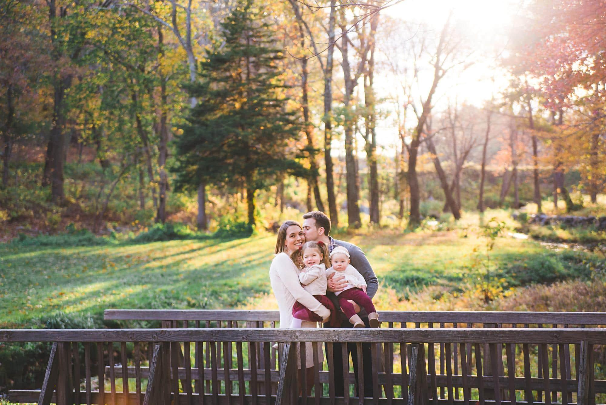 Family of 4 kissing on bridge outside Wayside Inn Grist Mill