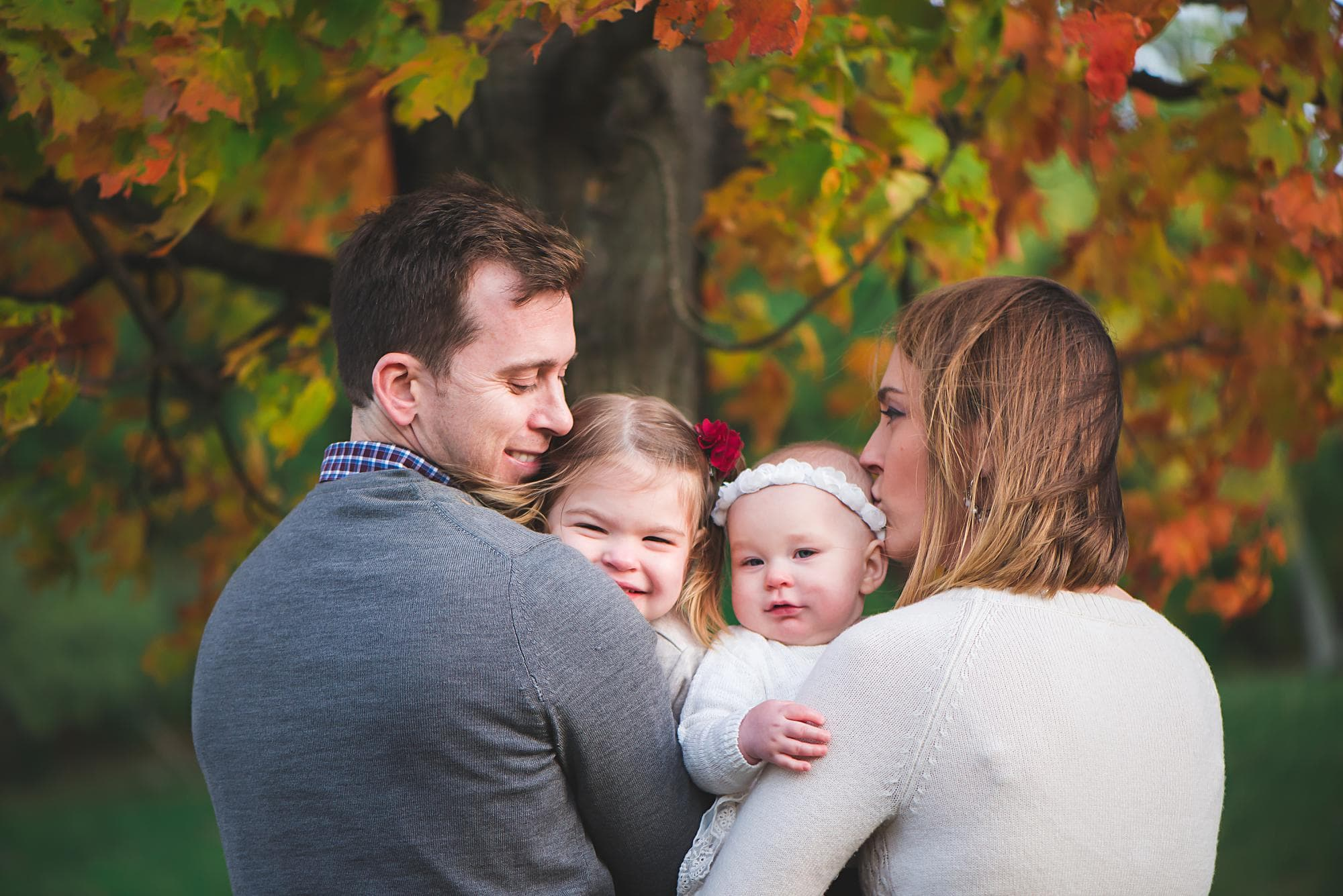 Mom and dad holding daughters under tree with orange leaves