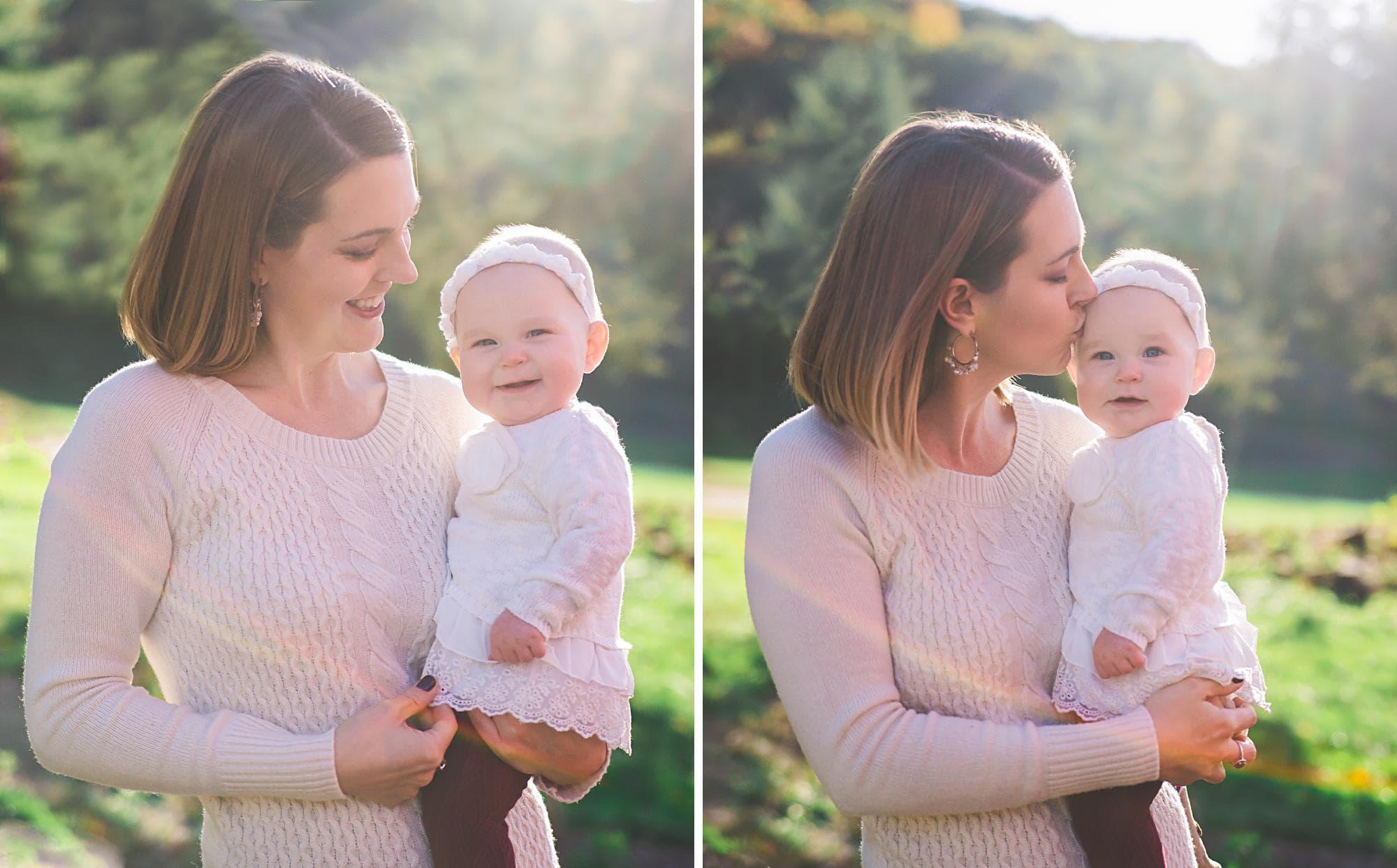 Mom kissing infant girl outside
