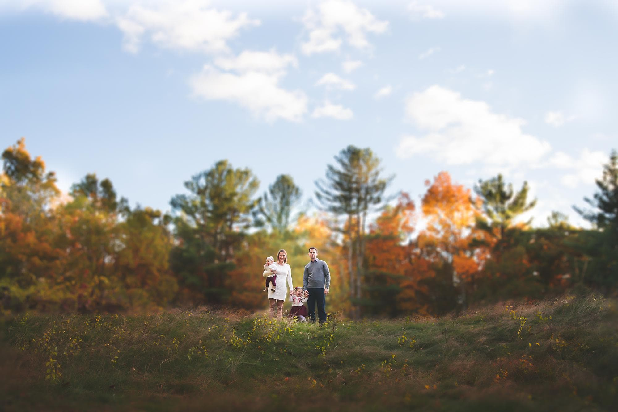 Family of 4 standing on a hill with Fall colors