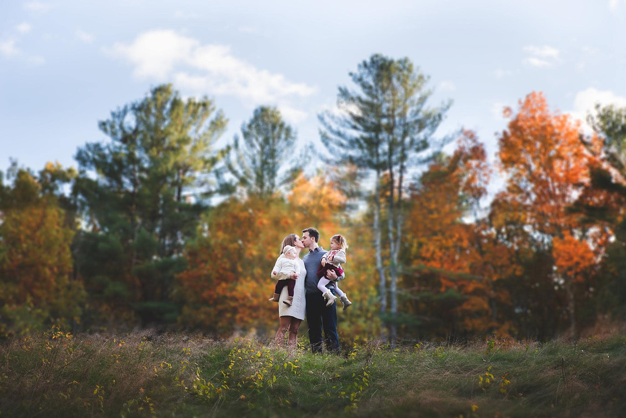 Family of 4 with mom and dad kissing outside with Fall colors