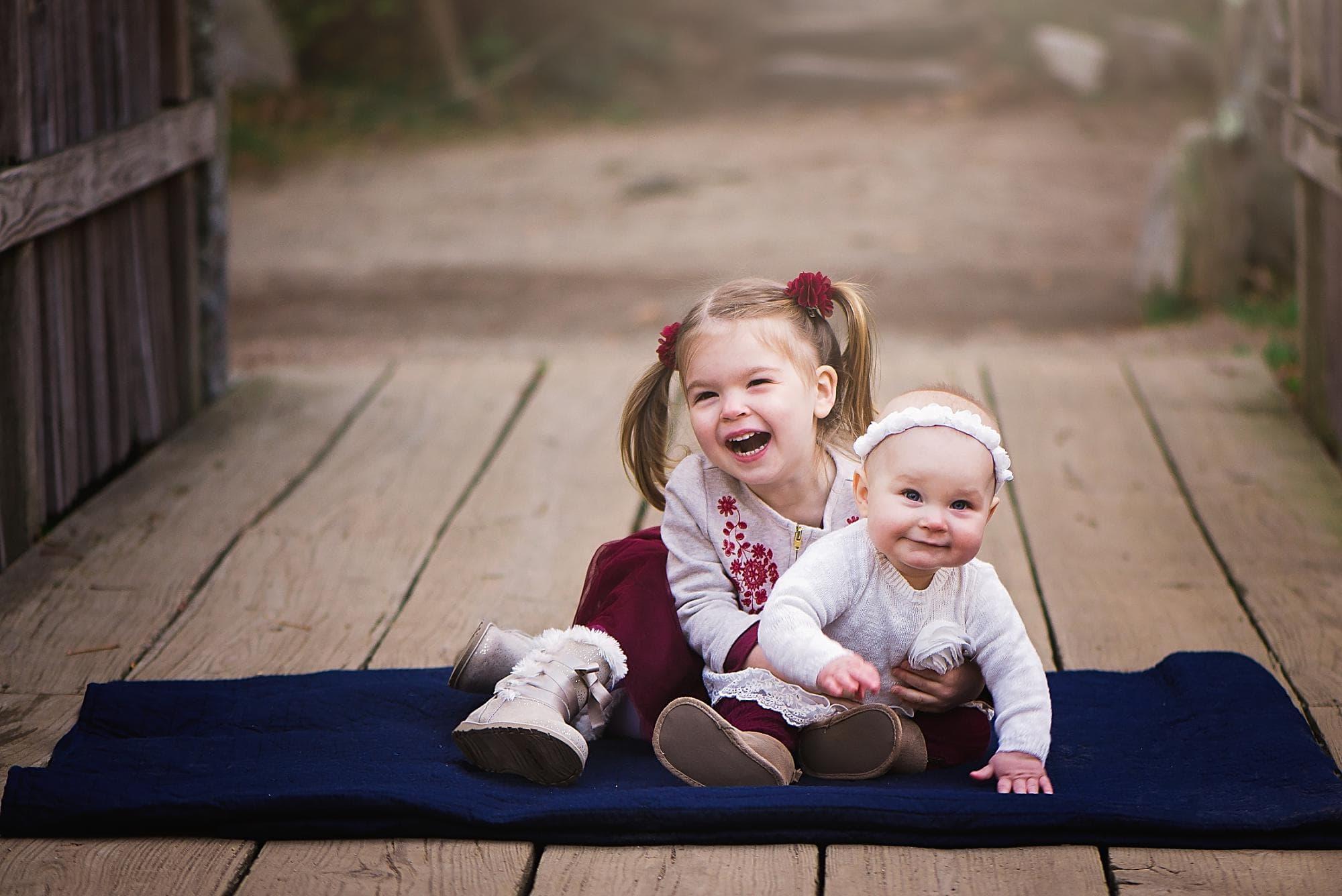 Sibling girls hugging on a bridge