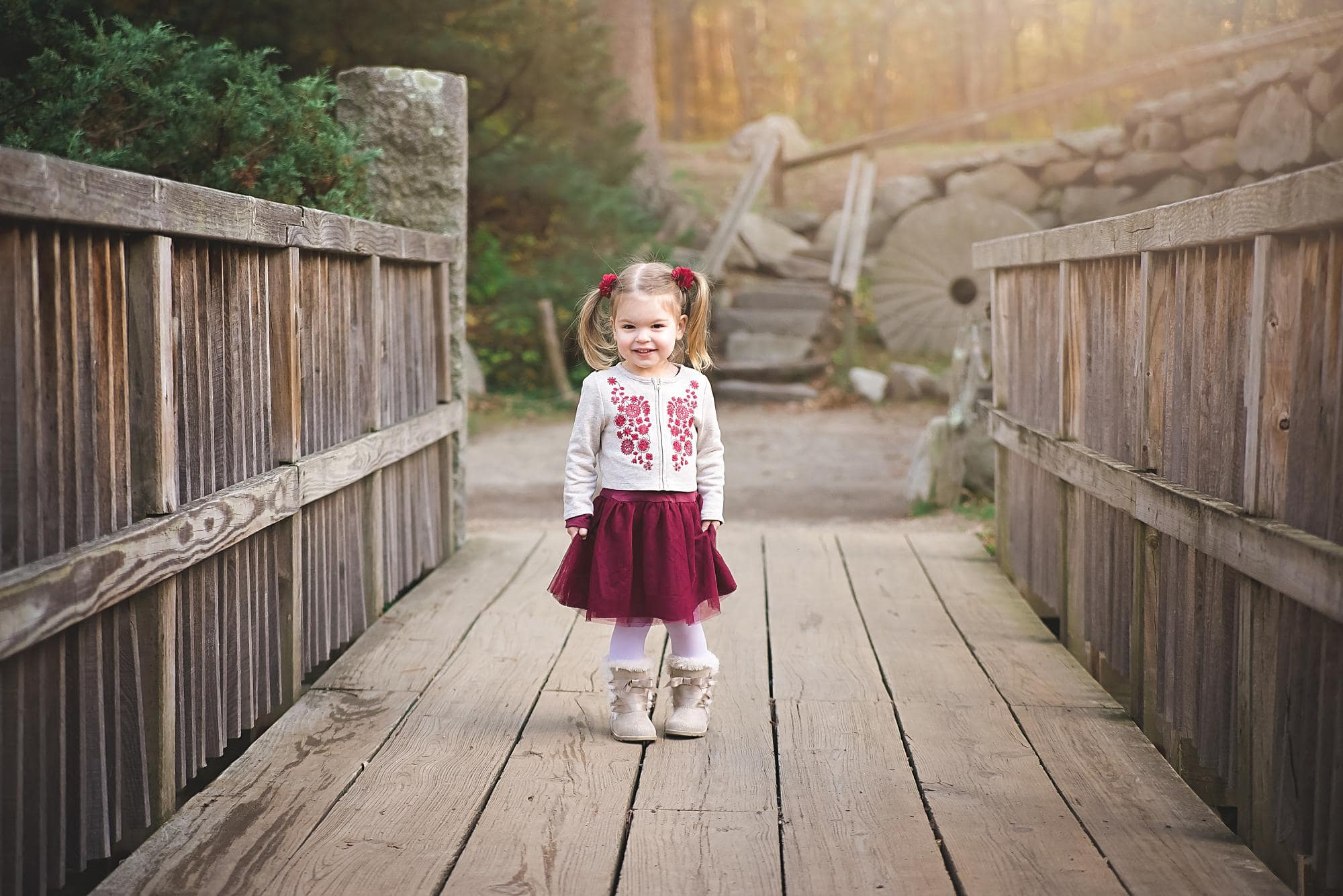 Toddler girl in a white and red dress on a bridge