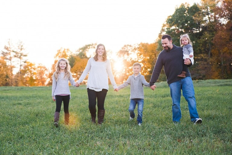 Family of 5 holding hands walking towards the camera near sunset
