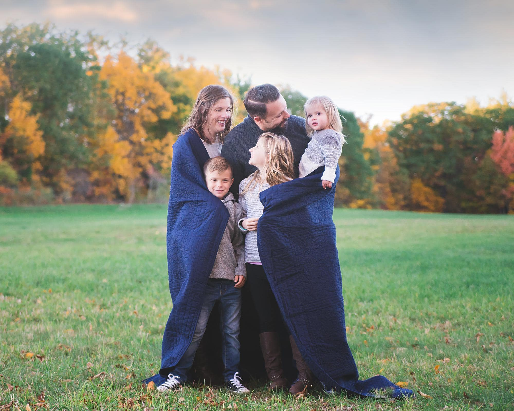 Family of 5 hugging in a blue blanket outside in the Fall