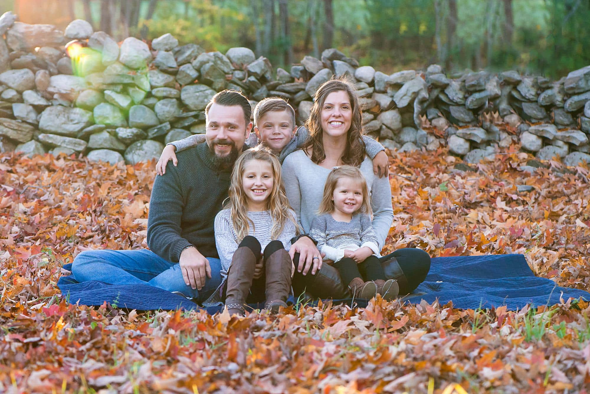 Familt of 5 sitting in leaves with Fall colors