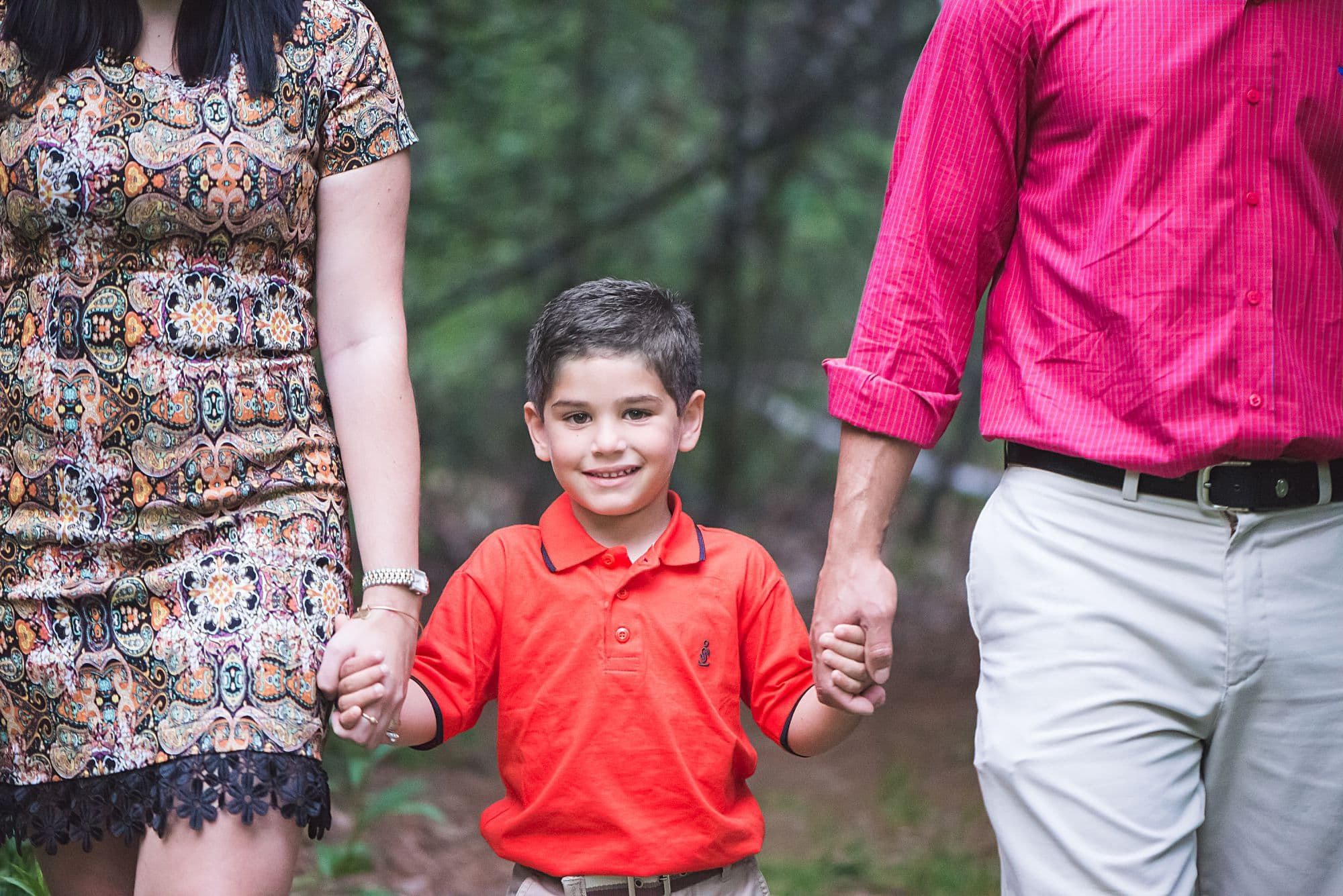 Close up portrait of boy holding his parents hands in an on location portrait session
