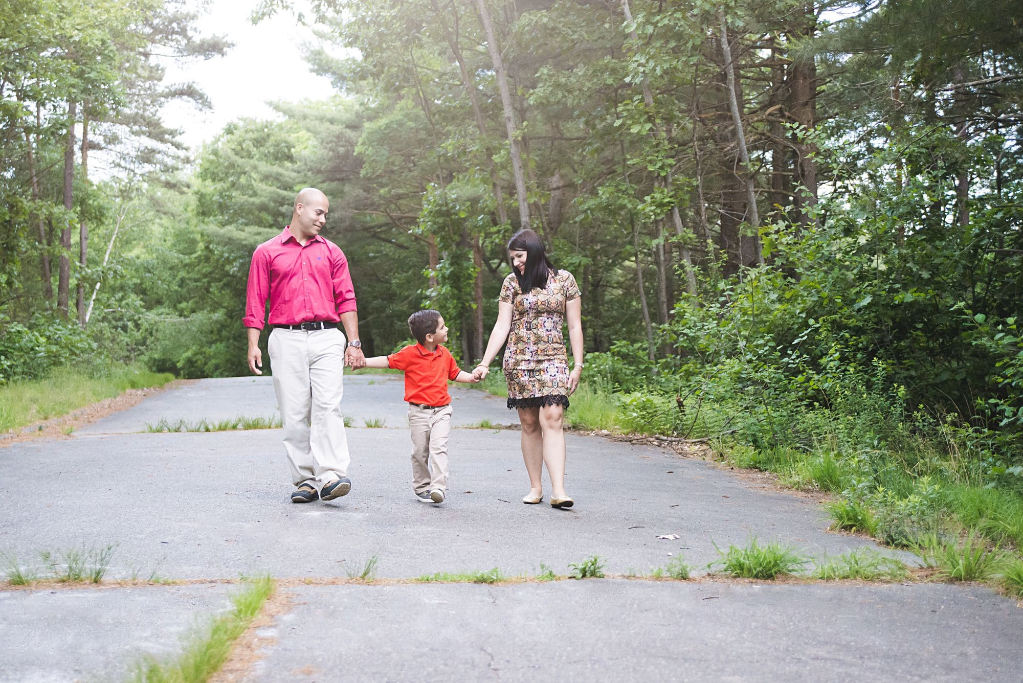Family of three casual photo walking through a park with beautiful trees and sunlight wearing pink and orange