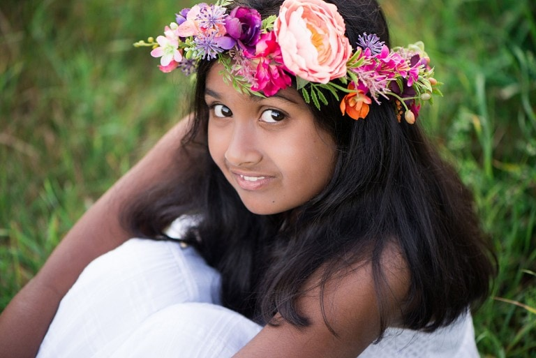 Close up headshot of tween girl with beautiful floral crown in her long dark hair