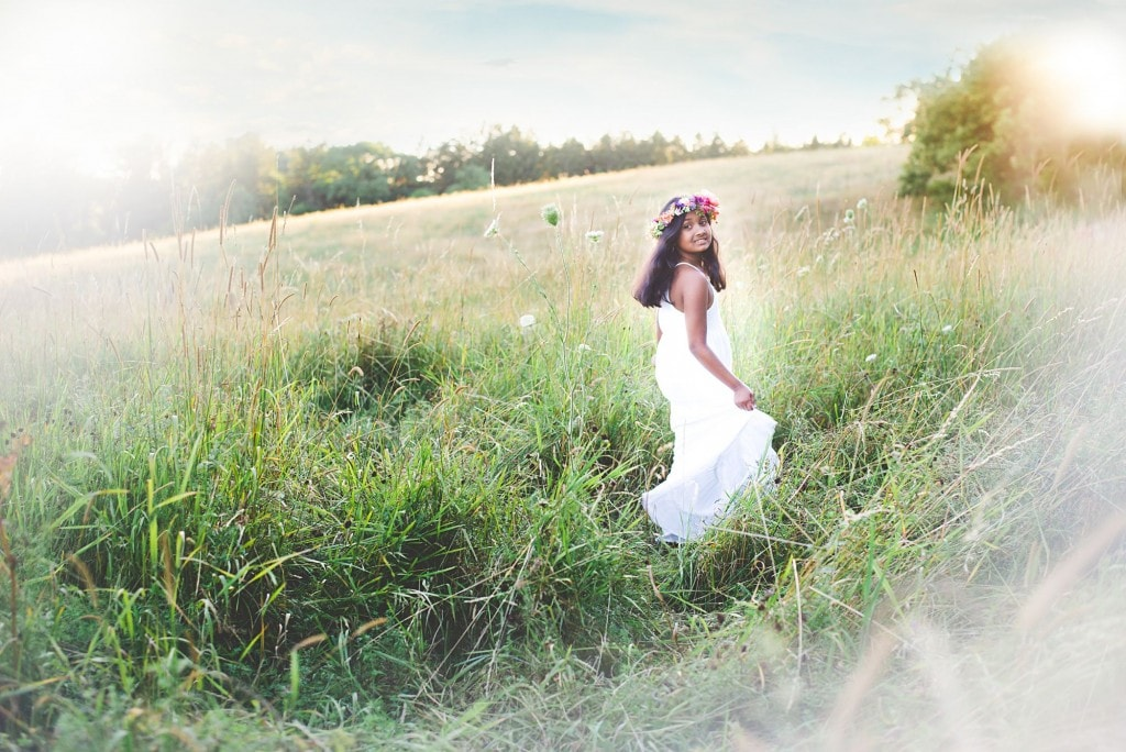 Tween girl twirling in a grassy field wearing a white dress and pink floral crown
