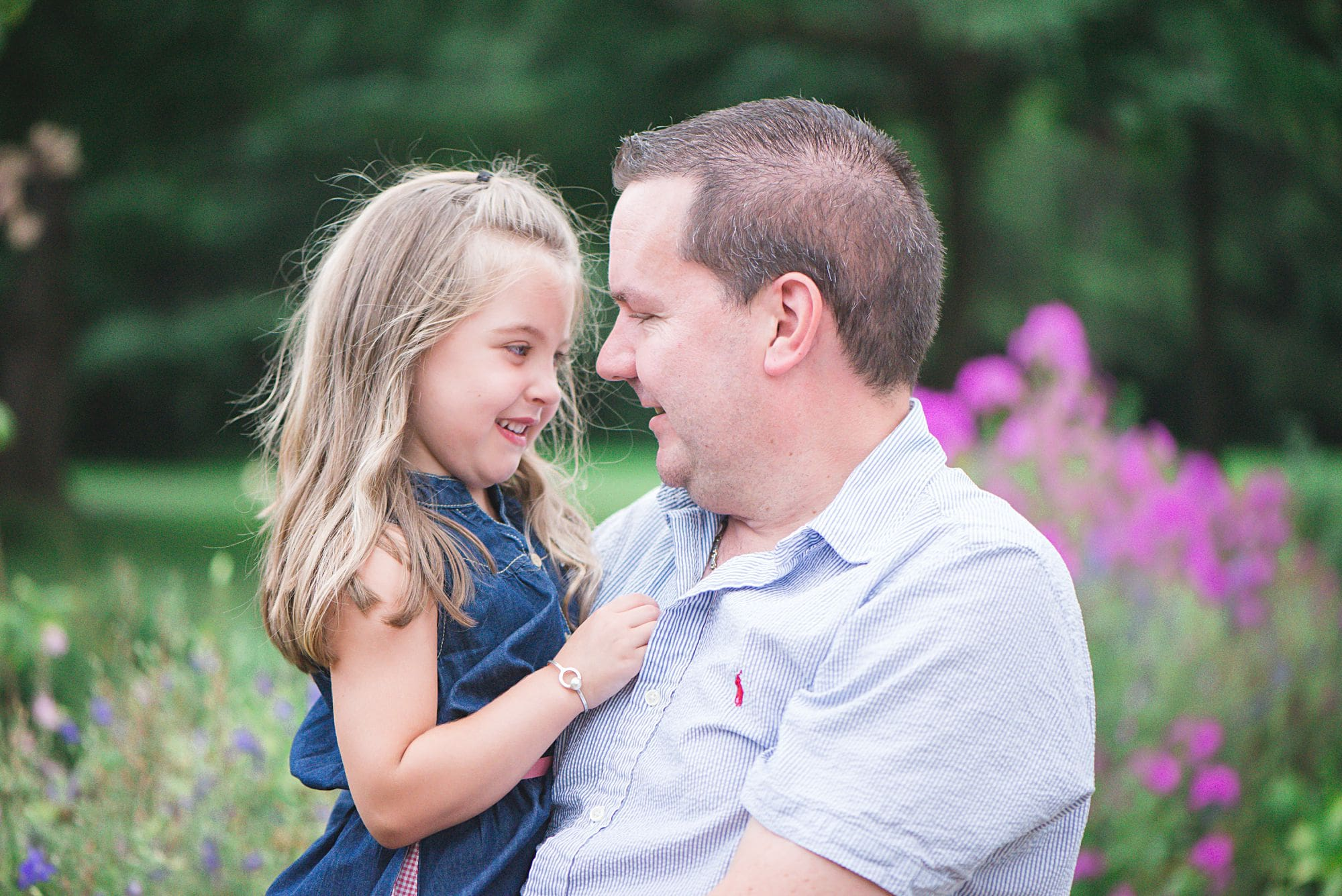Daddy daughter portrait in a casual lifestyle pose outside in a botanic garden