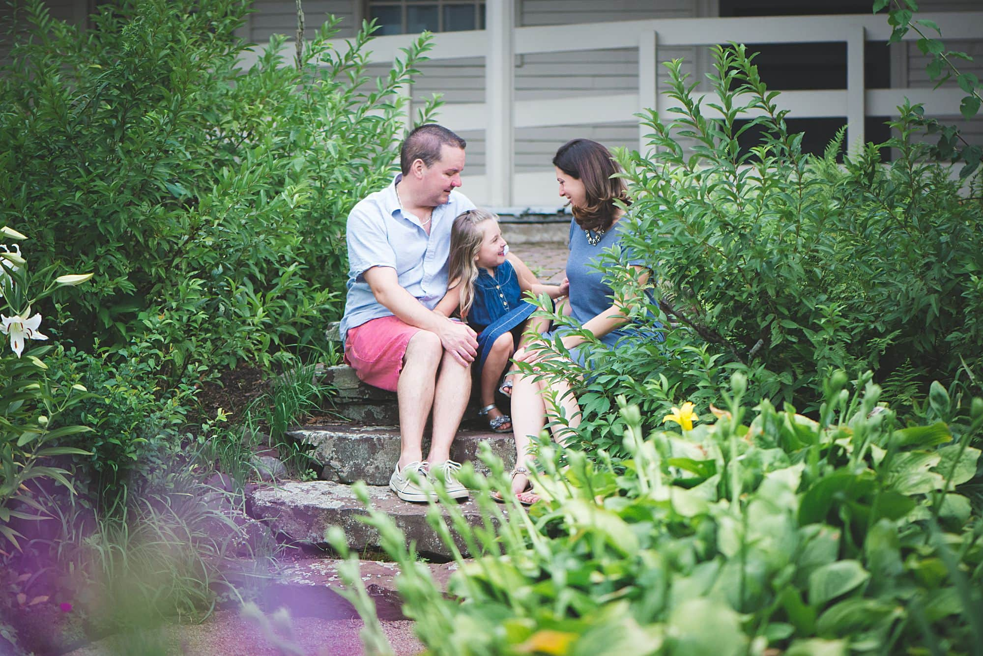 Family talking together on stone steps in a lush green garden