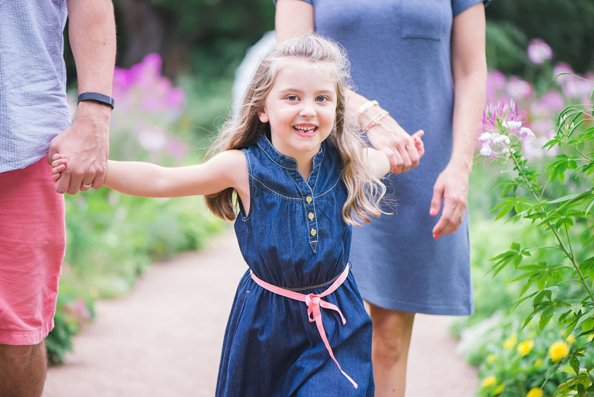 Close up of little girl holding hands with her parents walking on a path, wearing a blue dress with pink belt