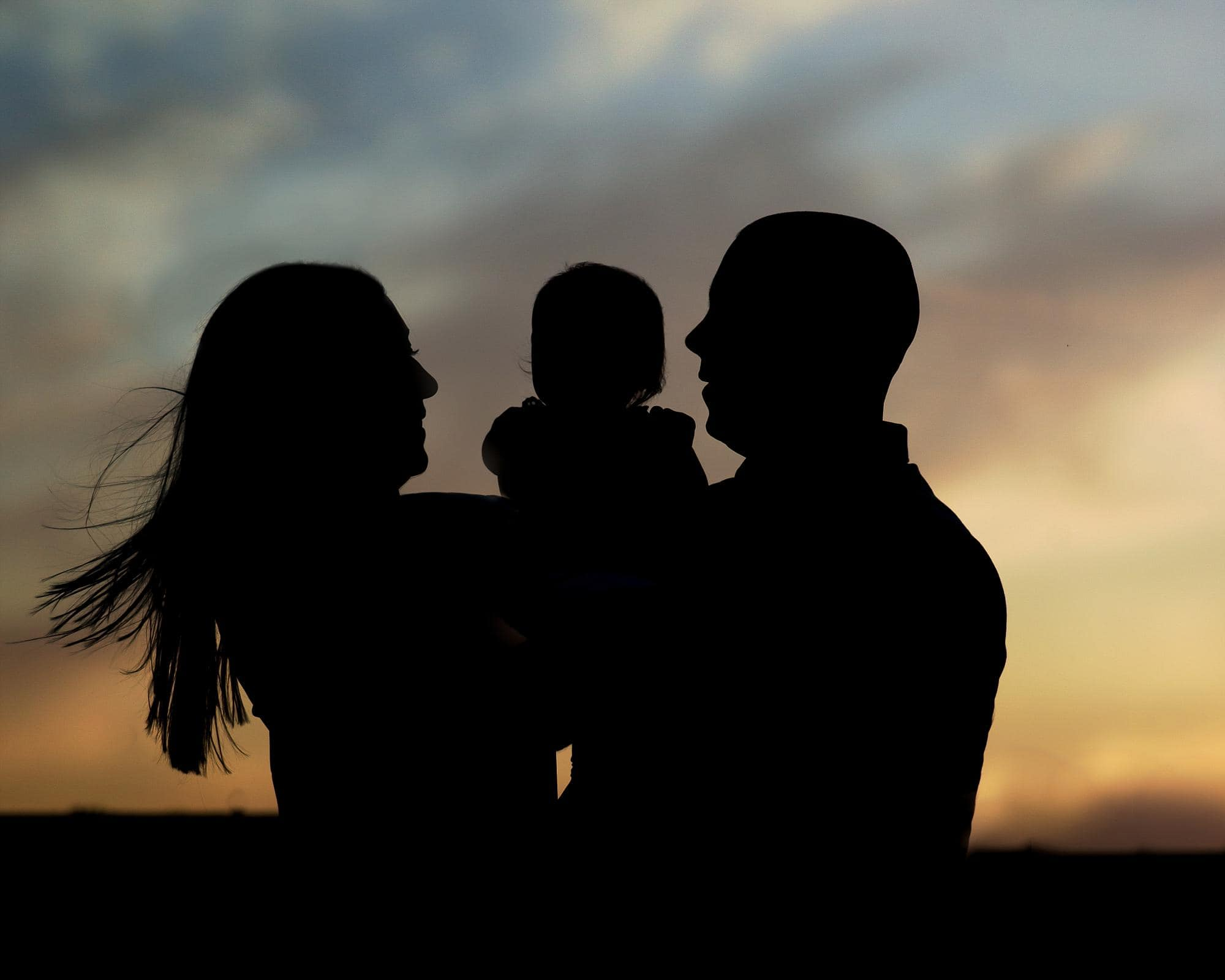 Family of 3 silhouette at sunset