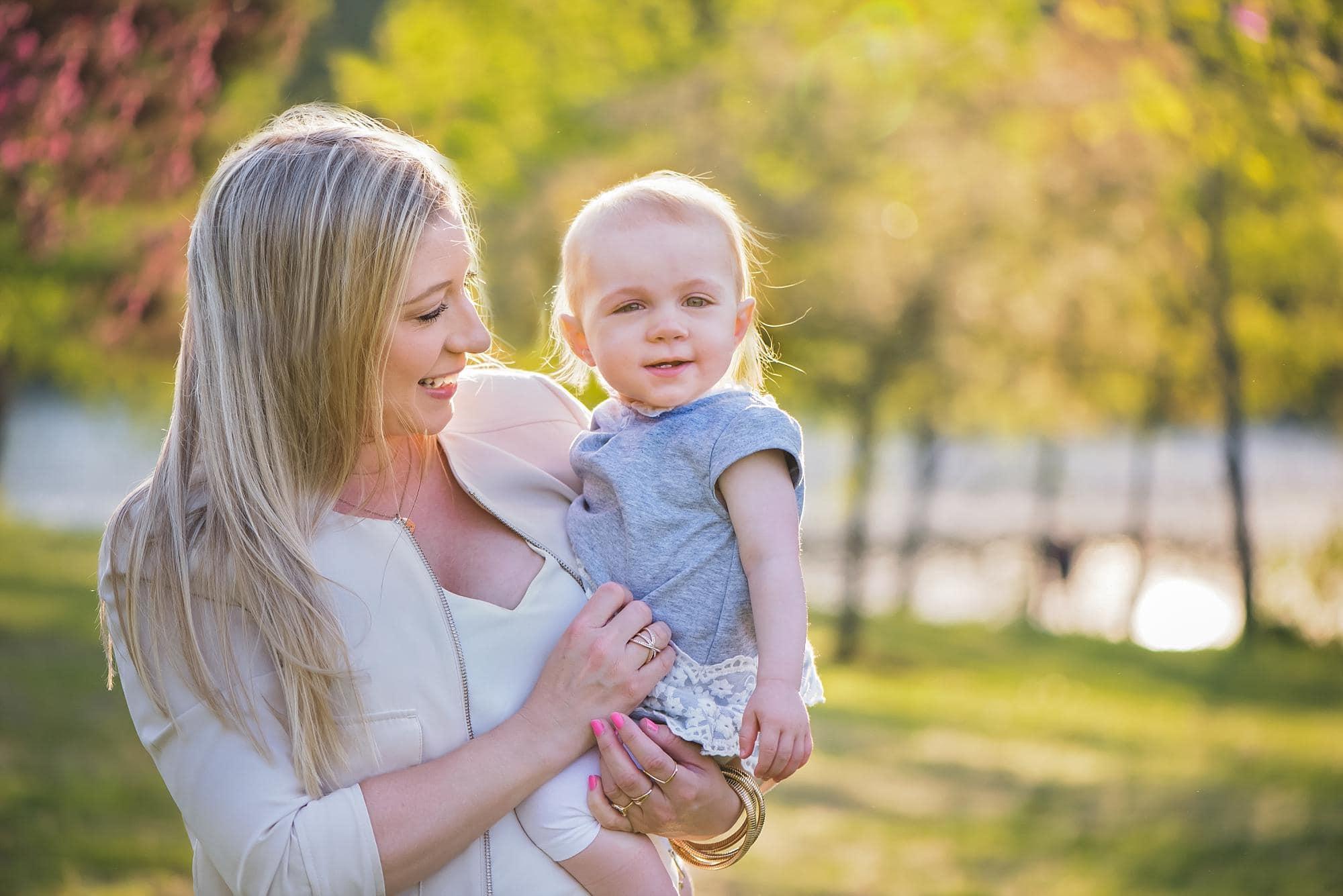 Mom holding little girl outside