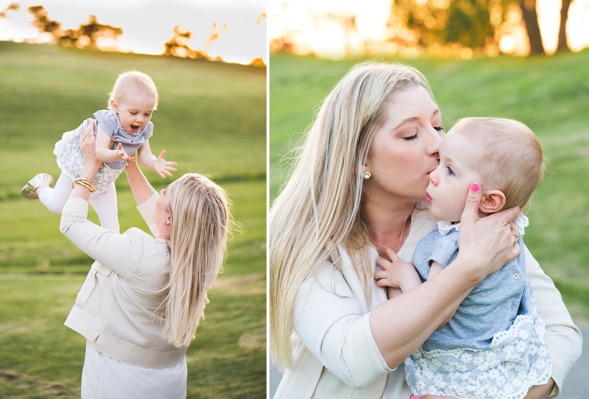 Mom holding up toddler girl outside