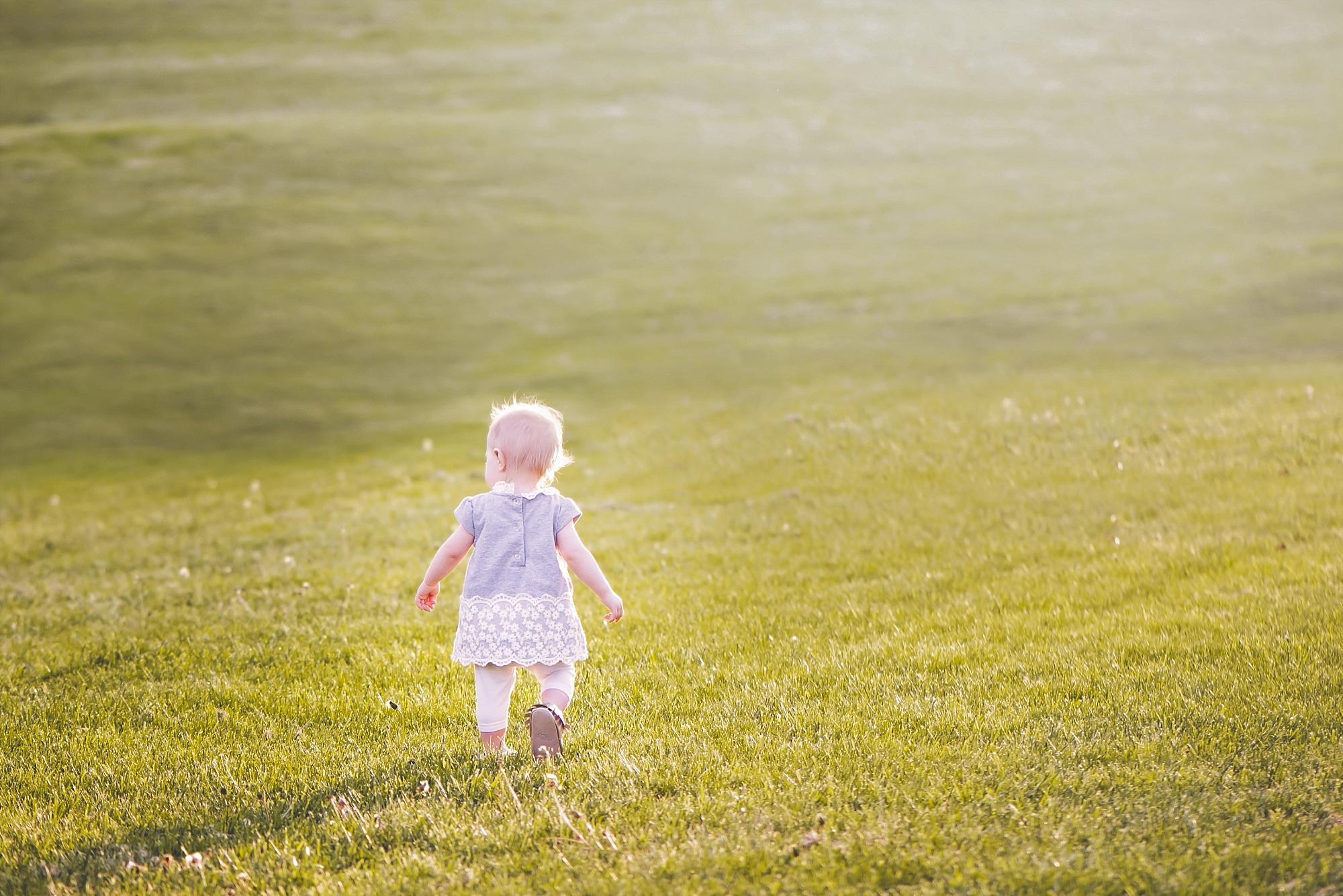 Toddler girl walking away in a field