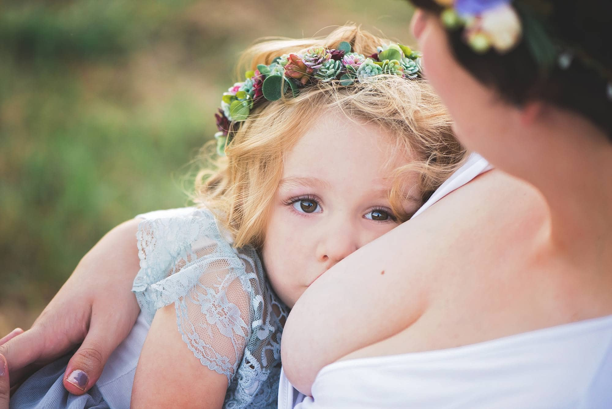 Closeup of breastfeeding toddler girl with flower crown