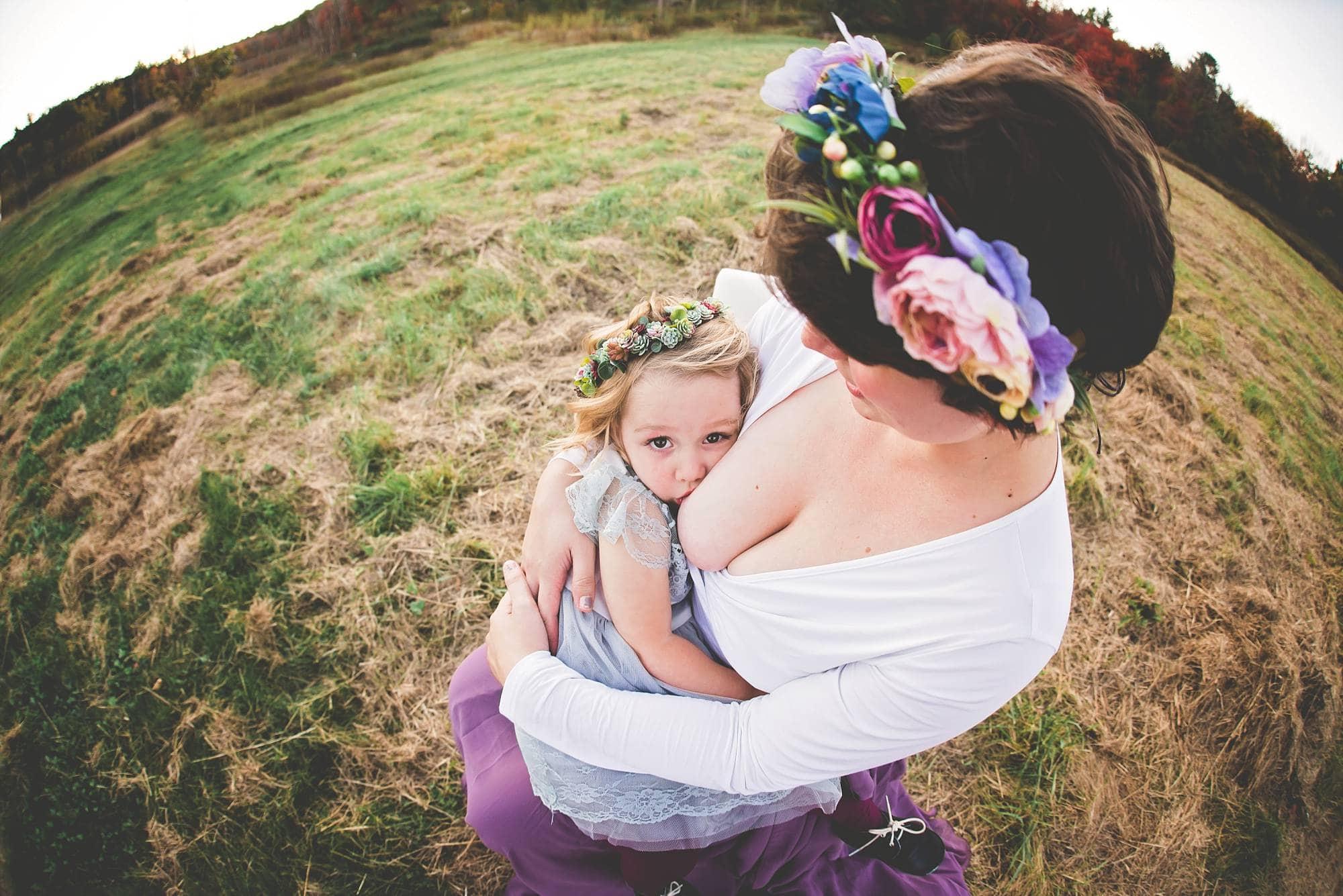 Mom breastfeeding toddler girl looking at the camera