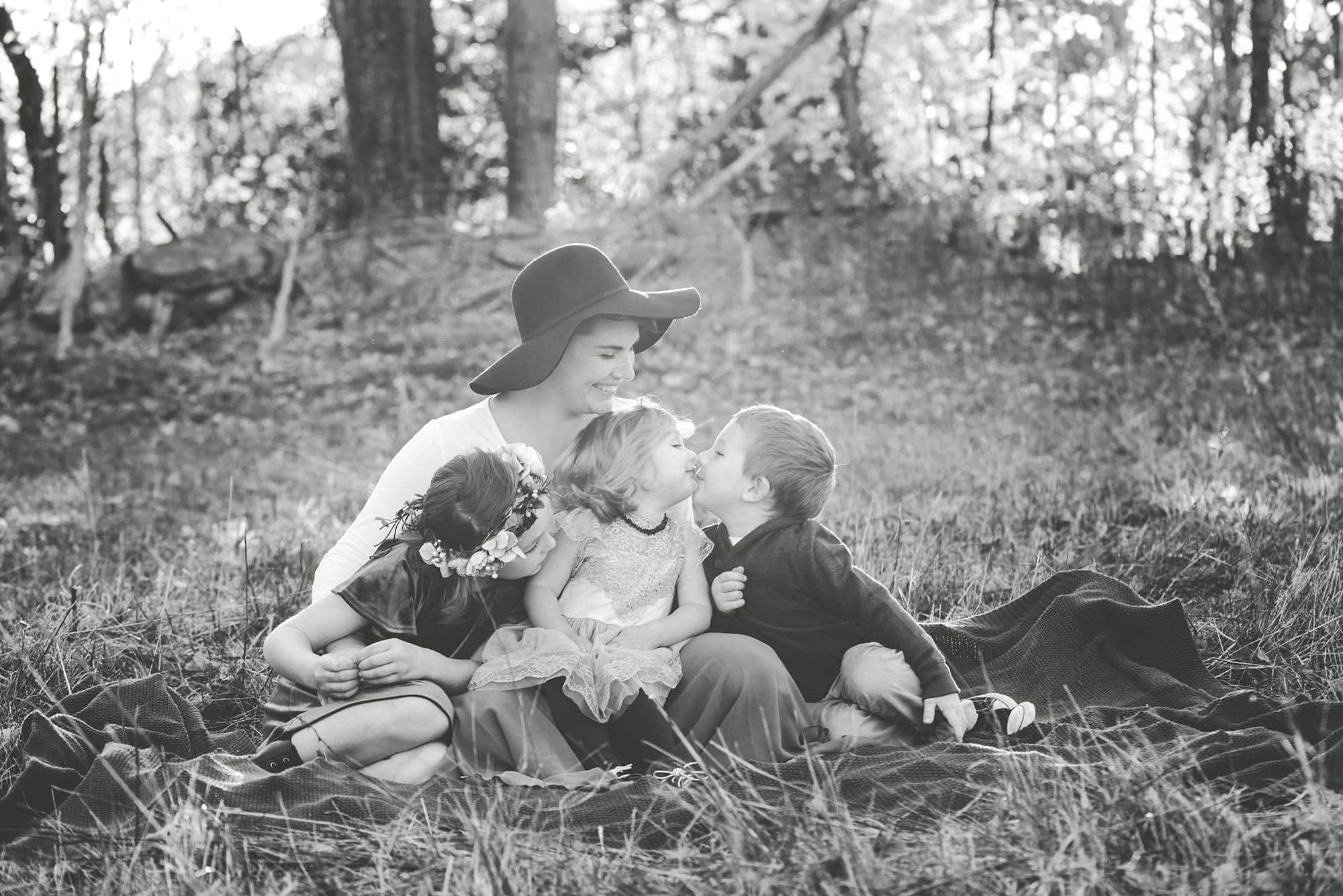 Black and white photo of mom and her 3 kids on a blanket in a field