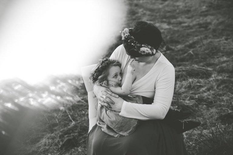 Black and white photo of mom breastfeeding toddler girl