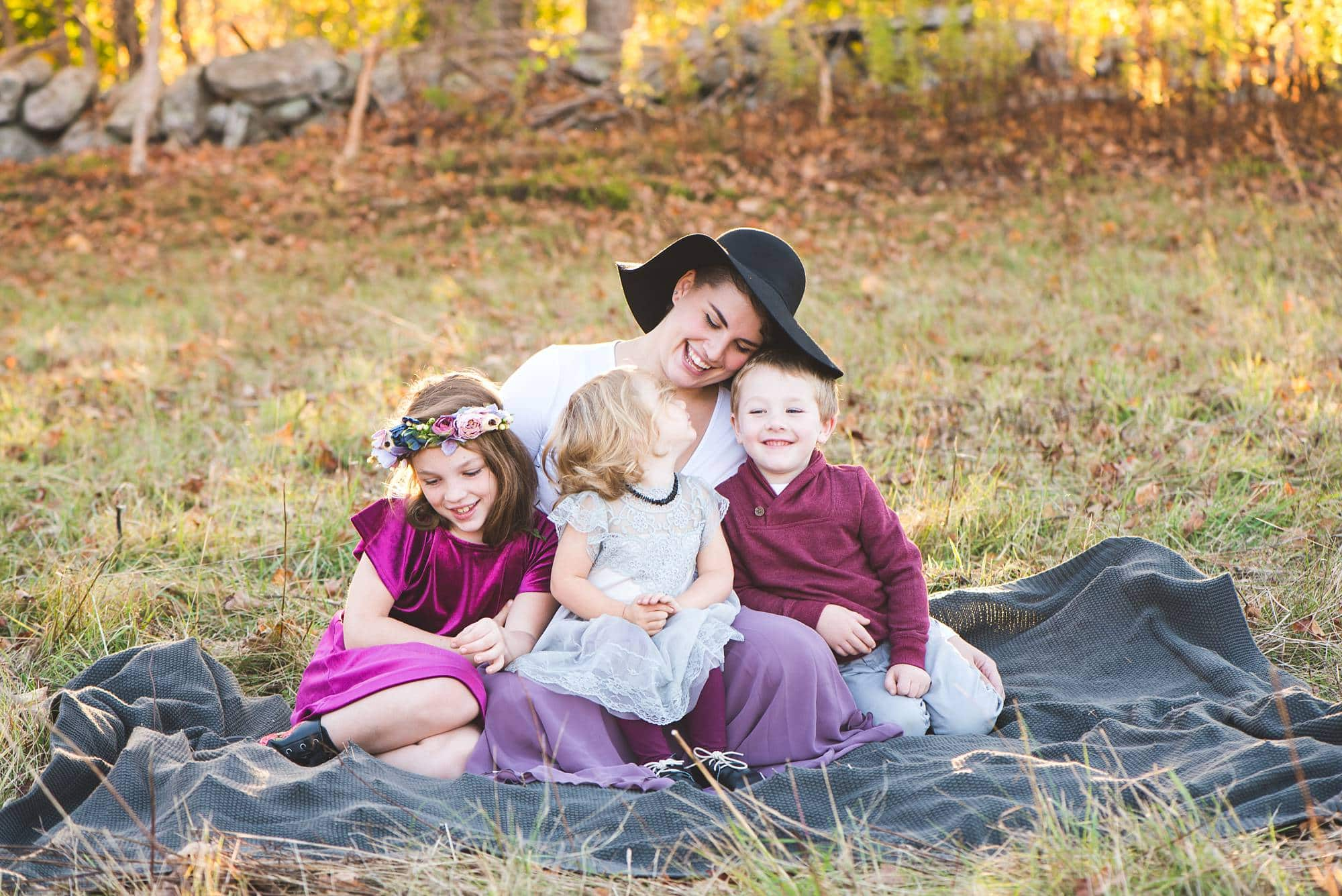 Mom snuggling with 3 kids on a blanket in a field