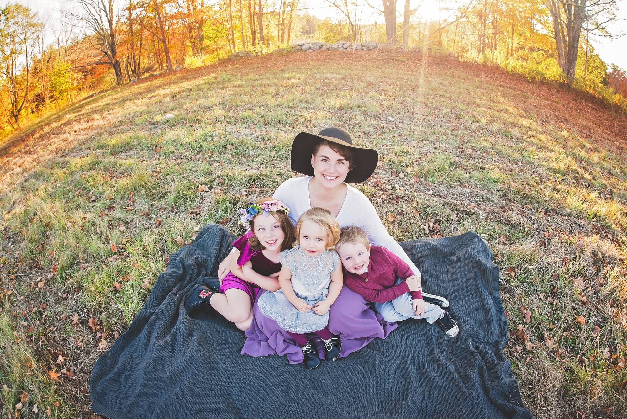 Mom sitting with her 3 kids on a blanket with fall colors