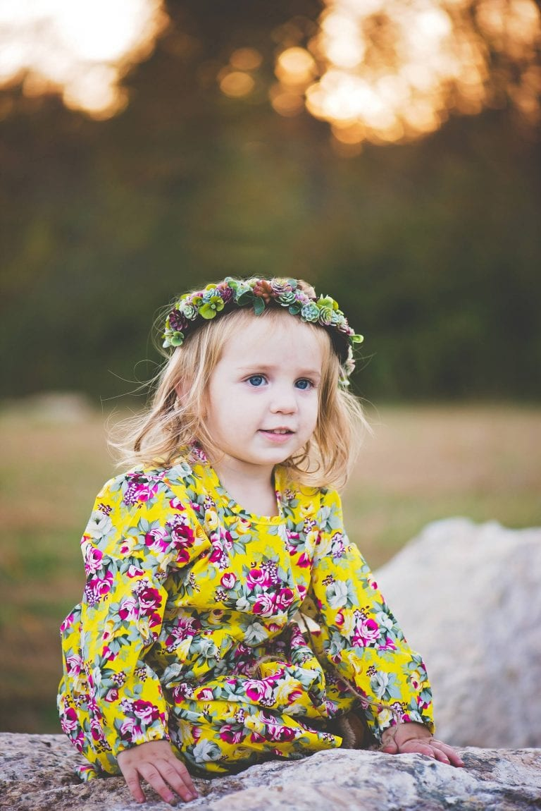 Toddler girl on a rock with flower crown on